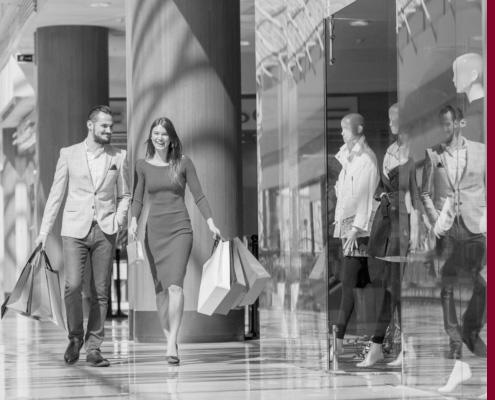 Paar mit Einkaufstaschen in Einkaufszentrum